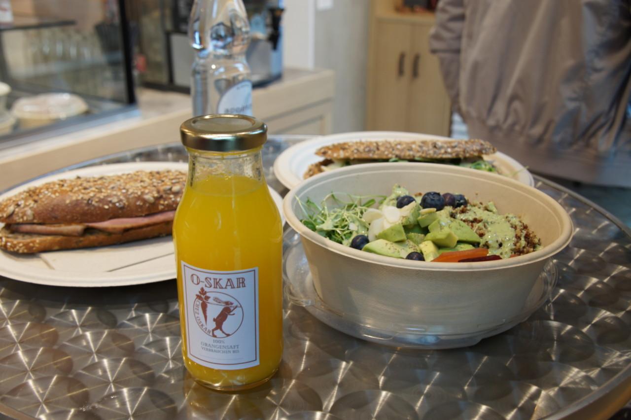 Das feine Mittagsangebot «chez Oskar»: Knusprige Sandwiches, vegane Salat-Bowl und frischgepresster Orangensaft. Foto: Lunchgate/Max