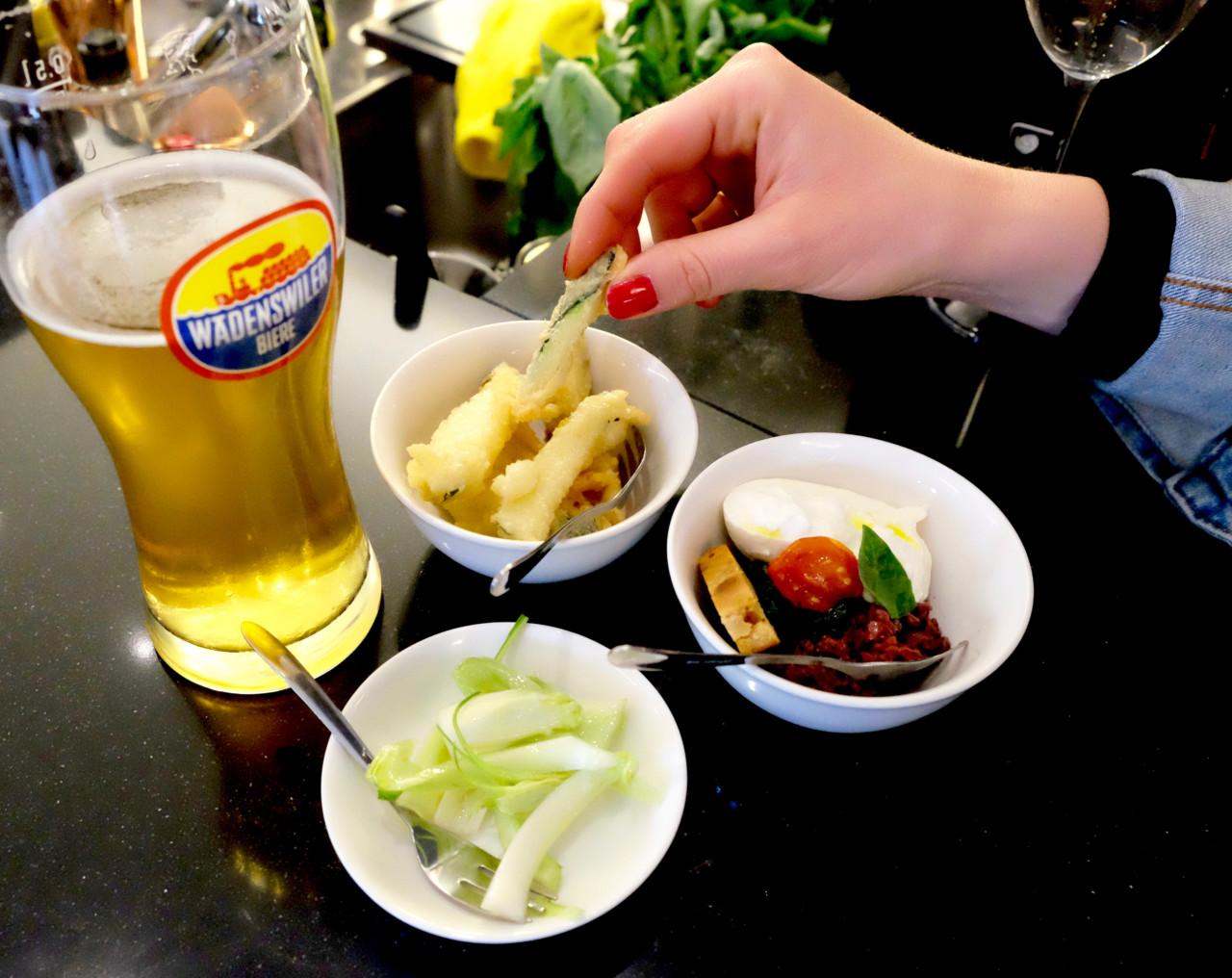 Feine Häppchen: Luftig frittierte Zucchini, knackiges Fenchelgemüse und cremige Burrata auf Krautstiel und Taggiasche Oliven. Und dazu gibt's hier frischgezapftes Wädibrau!