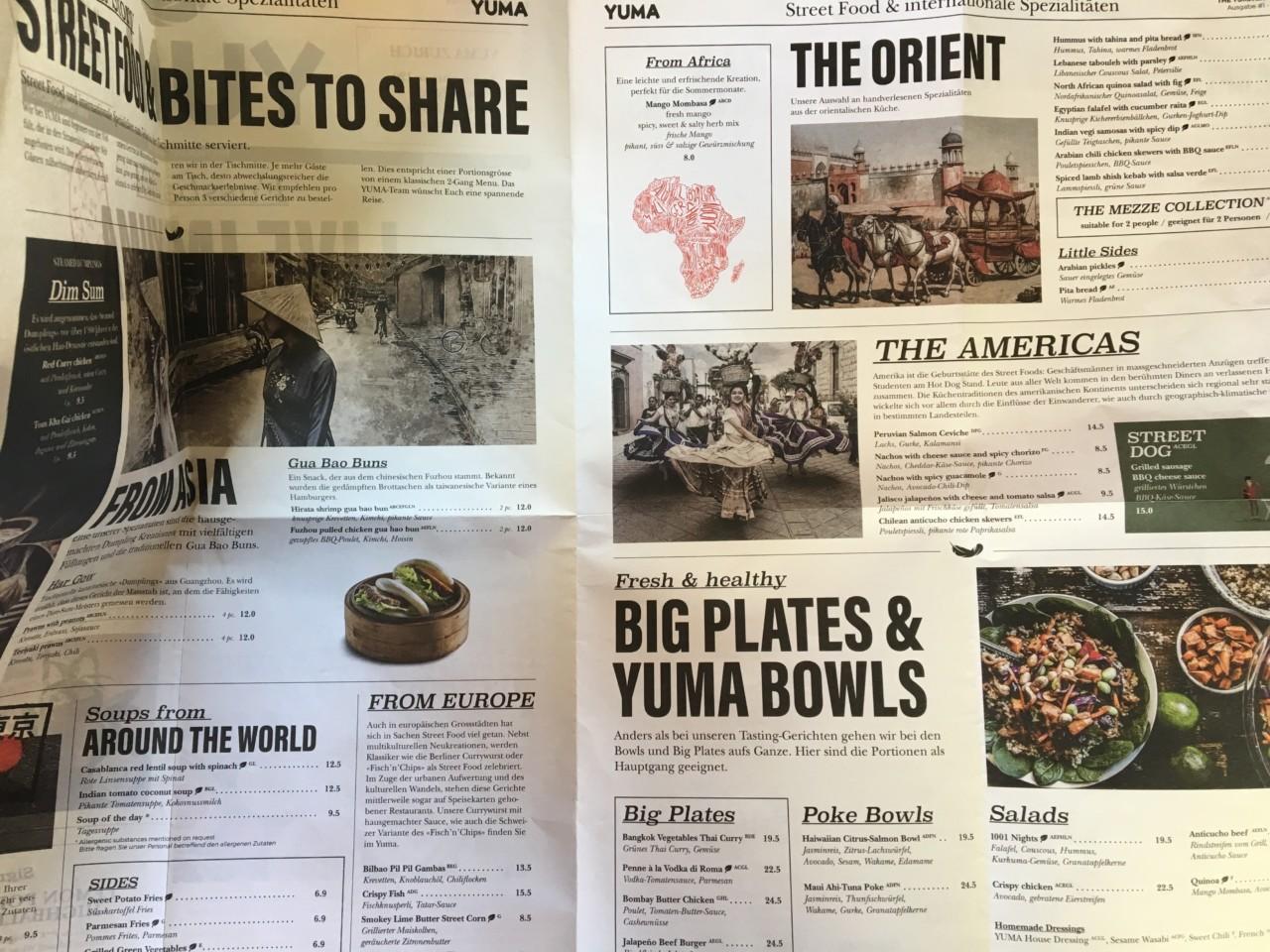 Statt einer öden Karte gibt es hier eine Menü-Zeitung inklusive spannender Infos zur Herkunft der Gerichte. Foto: Lunchgate/Simone