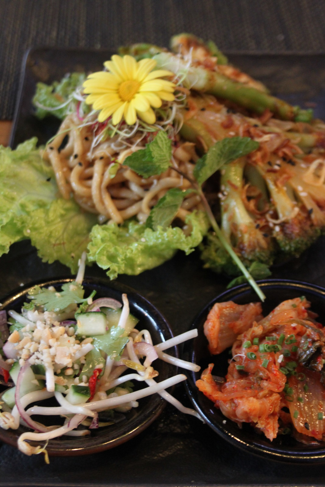 Das Broccolisteak serviert mit Röstzwiebeln, schwarzen und weissen Sesamsamen und frischer Kresse. Foto: Lunchgate/Selina